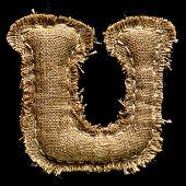 Linen or hemp vintage cloth letter U isolated on black background