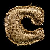 Linen or hemp vintage cloth letter C isolated on black background