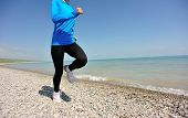 Runner athlete running on stone beach of qinghai lake. woman fitness jogging workout wellness concep