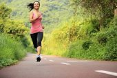 young fitness woman running at forest trail