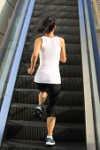 Runner athlete running on escalator stairs .