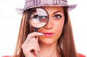 Woman with hat looking through magnifier glass, isolated on white