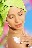 foto of turban  - Attractive woman rubbing a body lotion on her arm - JPG