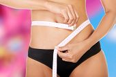 Slim fit woman with measure tape measuring her waist