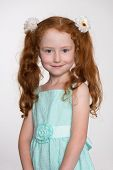 Wonderful red haired little girl on a gray background.