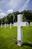 pic of headstones  - White headstone of an unknown soldier and US flags at the American War Cemetery in Luxembourg - JPG