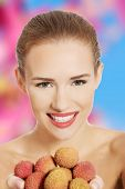 Beautiful topless caucasian woman holding fist of lychee