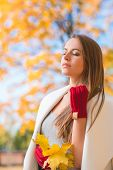 Young woman savoring the beauty of autumn standing with closed eyes in a park against a background of colorful yellow foliage