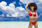 Woman Wearing Sunhat and Red Bikini Standing on Tropical Beach and Looking into the Distance