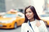 Young urban professional business woman in New York City Manhattan. Woman walking in street wearing coat downtown with yellow taxi cabs in background. Multiracial Asian Caucasian businesswoman in USA.