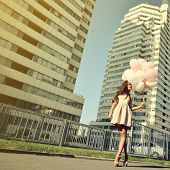 Beautiful young girl holding colored balloons over high-rise building. Urban teenage background. Ton