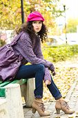 Young Beautiful Woman Sitting On A Bench In A City Park
