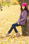 stock photo of knitted cap  - Young stylish smiling woman dressed in oversized knitted sweater skinny jeans peaked cap and heels having rest in city park - JPG