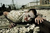 a scary zombie crawling by the railroad tracks