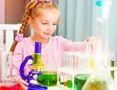 cute little girl with varicolored flasks for chemistry