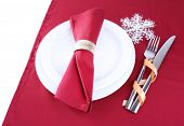 White plates, fork, knife and napkin on burgundy tablecloth isolated on white