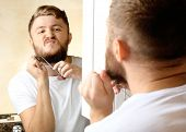 stock photo of shaved head  - Young man shaving his beard in bathroom - JPG