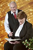 A senior couple reading the Bible together before a bank of diagonal gold lights with holly in the f