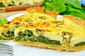 Pie with spinach and olives on plate