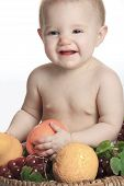 Happy little baby girl with fruits on the basket