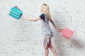 Amazing blond girl is going shopping with couple of colorful bags in her hands.
