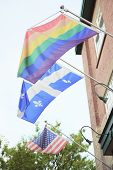 A gay pride flag hanging from a building Quebec