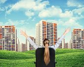 Businesswoman sitting on office chair. Green hills with buildings and sky