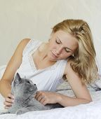 stock photo of caress  - Young beautiful woman caressing british cat on the bed - JPG