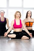 Group Of Three Females Sitting Cross-legged In Meditation In Class