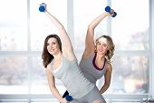 Two Sporty Young Females Having Aerobics Practice With Dumbbells