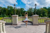 Ballerina Dancing At Park, Standing In Pointe Position. Outdoors, Spring