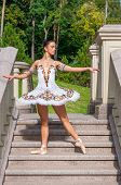 Ballerina Stands On Stairs, Standing In Pointe Position. Outdoors, Spring