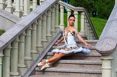 Ballerina Sits On Stairs, Standing In Pointe Position. Outdoors, Spring