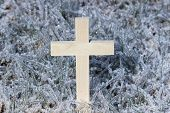 Wooden cross in ice covered grass background