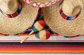foto of sombrero  - Mexican scene with sombrero straw hat maracas and traditional serape blanket or rug - JPG