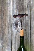 Vintage Corkscrew Removing Cork From Wine Bottle With Wood Background