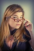 image of dork  - Cute nerdy girl with reading glasses posing for a portrait - JPG