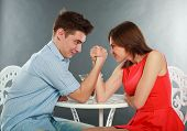 Young Happy Couple Challenge Fighting In Arm-wrestling At Table, In Studio Isolated On Gray