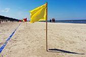 Yellow Flag And The Blue Line In The Sand Beach
