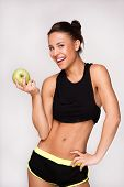 Mixed race sporty woman with an apple