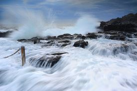 picture of gushing  - High tide and waves crashing onto the rocks bringing strong fast flowing water over the rocks and gushing past me into the rock pool at Kiama - JPG