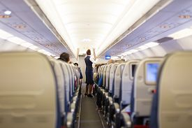 picture of aeroplan  - Interior of airplane with passengers on seats and stewardess in uniform walking the aisle - JPG