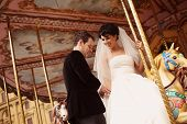 stock photo of amusement  - Bride and groom on carousel in amusement park - JPG
