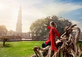 stock photo of qutub minar  - Woman in red costume pointing at Qutub Minar tower in Old Delhi India - JPG