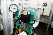 foto of manometer  - Industrial shot with a manometer and heating pipelines inside a water heating station - JPG