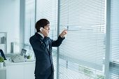 pic of blind man  - Businessman calling on the phone and looking out of the window through the blinds - JPG