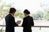 stock photo of coworkers  - Rear view of businessman showing something on the digital tablet to his female coworker - JPG