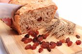 picture of fresh slice bread  - Slicing fresh baked wholemeal bread ears of wheat and heap of raisins lying on cutting board concept for healthy eating - JPG
