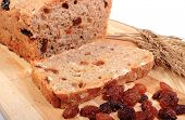 stock photo of fresh slice bread  - Slice of fresh baked wholemeal bread ears of wheat and heap of raisins lying on cutting board concept for healthy eating - JPG