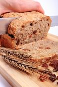 stock photo of fresh slice bread  - Slicing fresh baked wholemeal bread ears of wheat and heap of raisins lying on cutting board concept for healthy eating - JPG